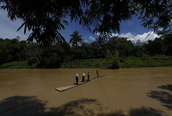 Students cross the Ciherang river on a bamboo raft while on their way home from school in Cilangkap village
