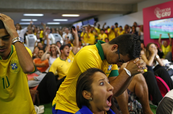Brazil soccer fans react as they watch the penalty shoot out of their team's victory against Chile during a 2014 World Cup round of 16 game, at Guarulhos International Airport in Sao Paulo